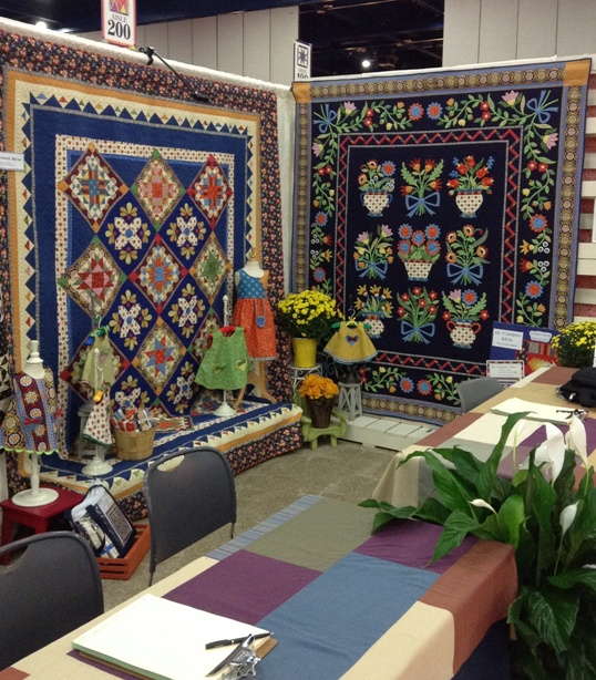 EL CAMINO REAL by Nancy Rink.  The BOM quilt is on the left; the  quilt on the right is an upcoming pattern, featured on the cover of Nancy's accompanying booth (coming soon!)